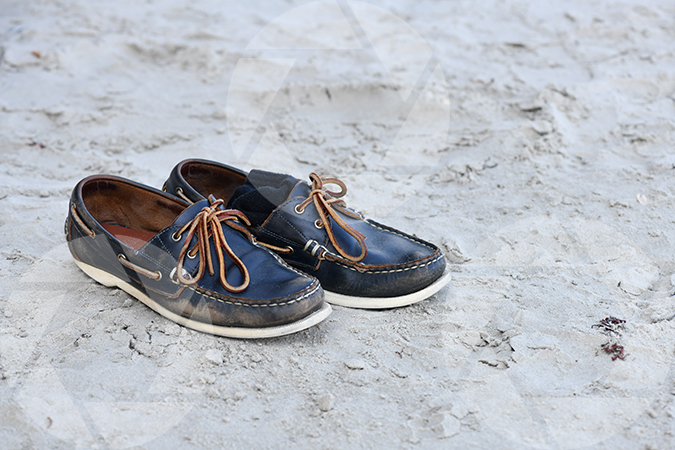 A pair of boat shoes on the sand at Galveston Beach