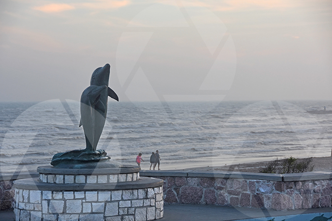 The dolphin statue on Galveston's Seawall Boulevard with the beach and beachgoers in the background.