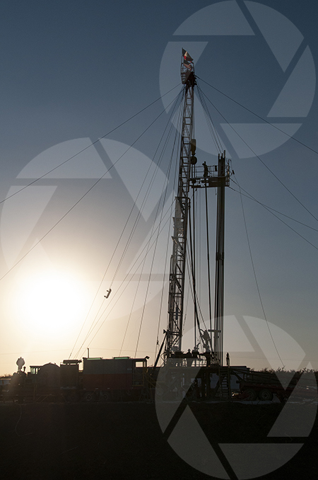 Exploration rig drilling ahead with the late afternoon sun low in the sky