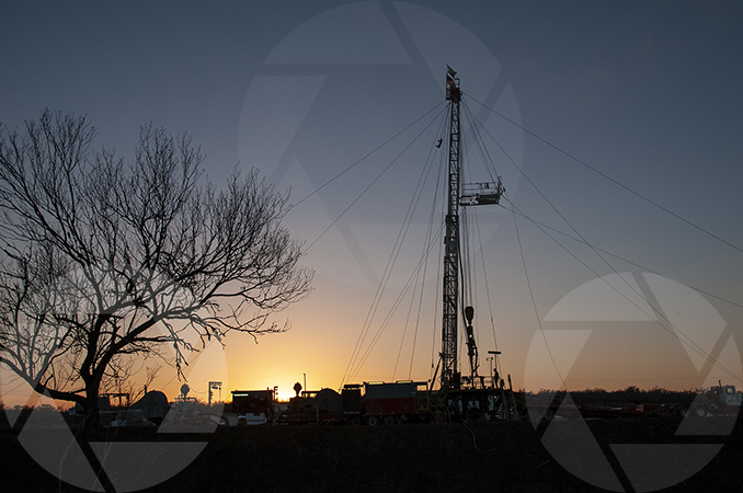 Oil rig at sunset with a mesquite tree in the foreground