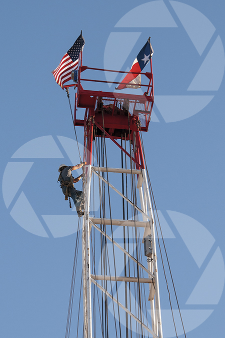 Oil rig worker climbing the derrick