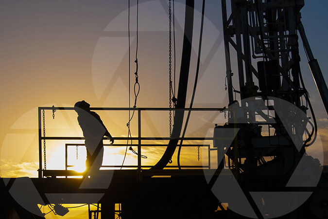 Oil rig worker rigging up an oil and gas drilling rig just before sunset.