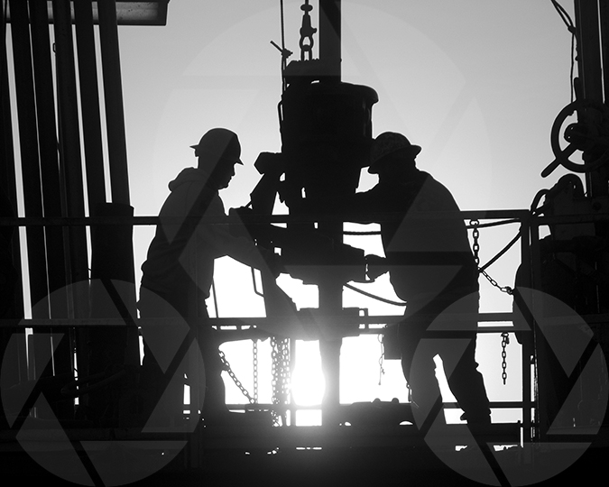 Black and white silhouette image of oilfield workers on the rig floor.