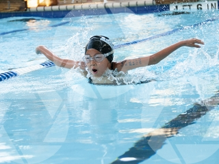 Photo of a female youth swimming butterfly at a swim meet