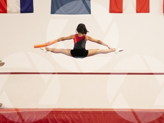 Female youth gymnast doing splits.