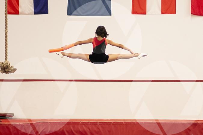 Female youth gymnast doing splits.