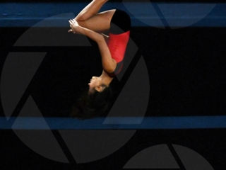 Female youth gymnast spinning in the air
