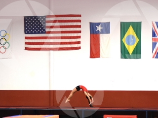 Gymnastics picture of a female youth doing a back layout under the American and Olympic flags