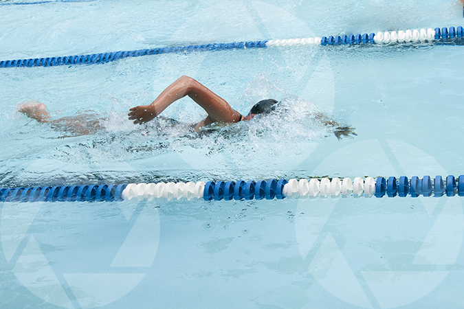 Female youth swimming freestyle at a swim meet