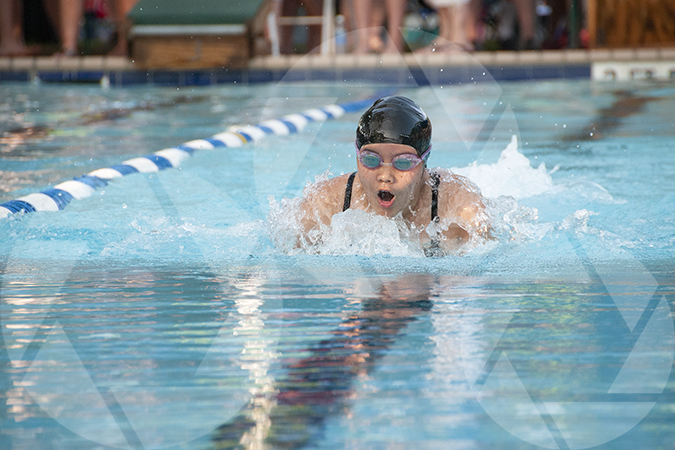 Youth sports photo of a female swimming breast stroke at a swim meet